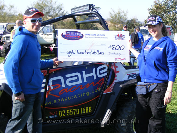 Krystal from Snake Racing and Phil hold the 4x4 Masters winners cheque in front of Polaris RZRs